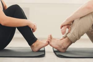 Two people on yoga mats touching feet
